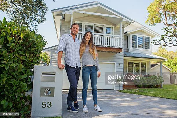 couple standing by their mailbox in front of new home