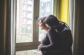 Couple standing by window, embracing