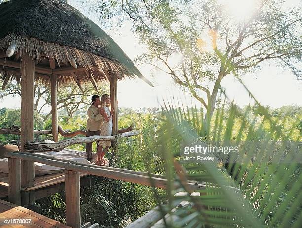 Couple Standing in a Holiday Home Enjoying the View Over the Jungle, Botswana, Africa