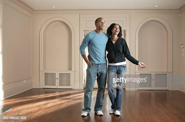 Couple standing in barren room, smiling