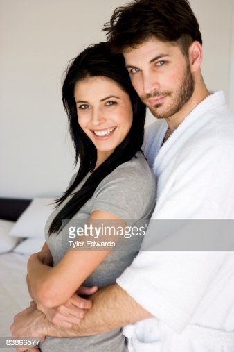 Couple standing in bedroom, man embracing woman : Stock Photo