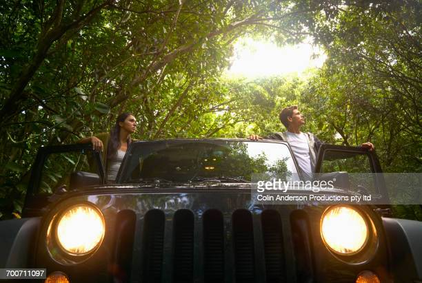 Couple standing in car in forest