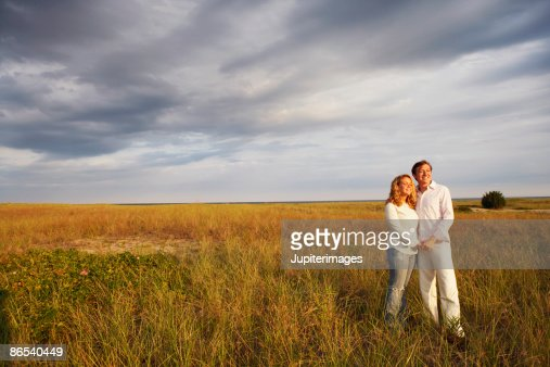 Couple standing in field : Stock Photo