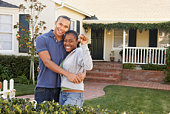 Couple standing in front of a house