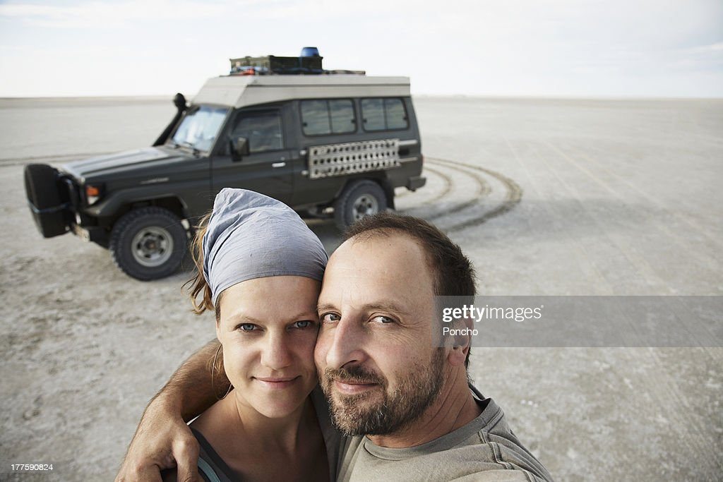 Couple standing in front of a Land Cruiser : Stock Photo