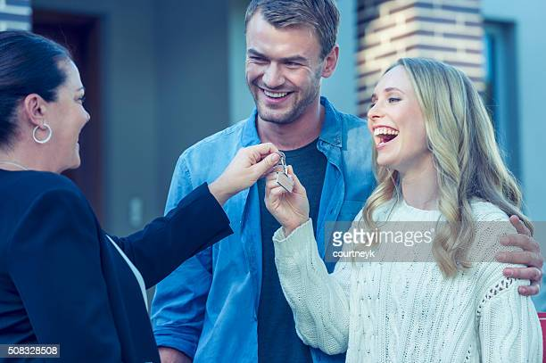 Couple standing in front of a new home with agent.