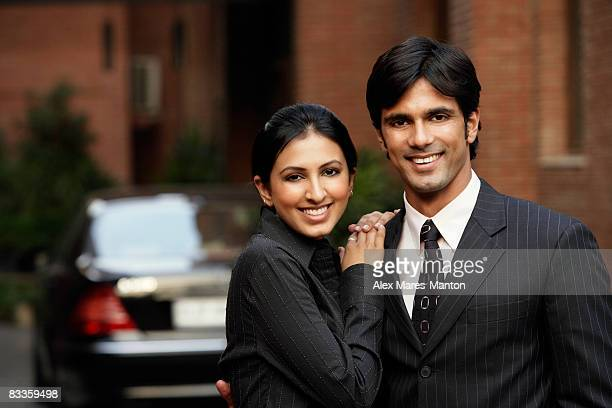 couple standing in front of car