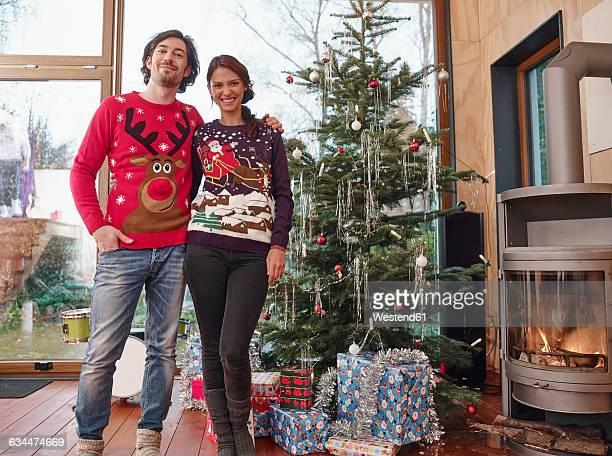 Couple standing in front of Christmas tree wearing Christmas jumpers