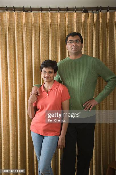 Couple standing in front of drapes