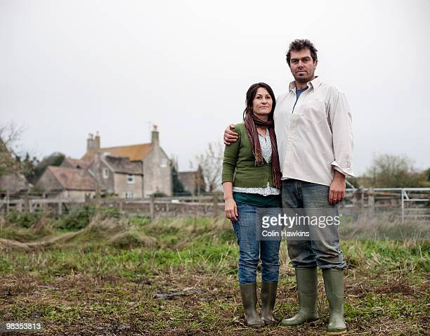 couple standing in front of farm house