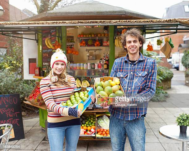 Couple standing in front of small juice bar.