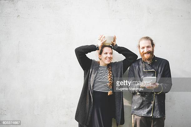 Couple standing in front of wall holding pots looking at camera smiling