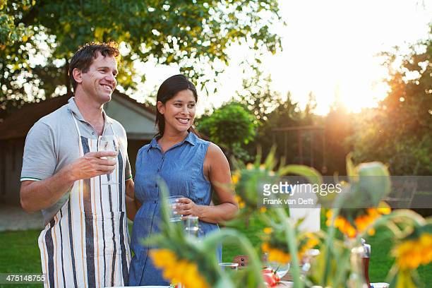 Couple standing in garden, drinking glass of water