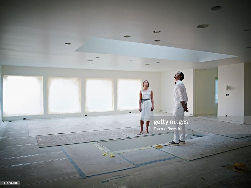 Couple standing in home looking into skylight : Stock Photo
