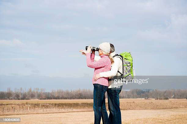 Couple standing in meadow with binoculars