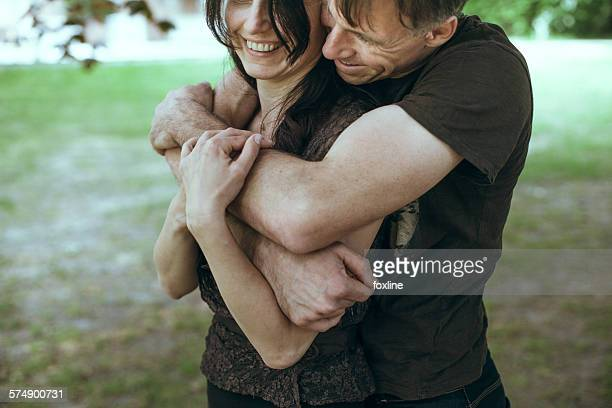 Couple standing in park hugging