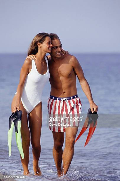 Couple standing in sea with flippers in hands
