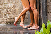 Concept of couple taking shower together, photo of couple's legs.