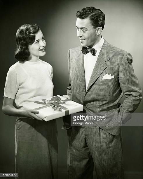 Couple debout dans le studio, femme tenant présents (B & W