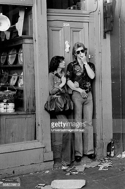 Couple standing in the doorway of a shop at Portobello Road market London August 1975