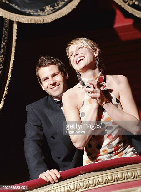 Couple standing in theatre box, smiling, low angle view
