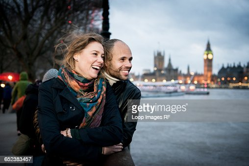 A couple standing looking across the River Thames with the Houses of Parliament in the background : Stock Photo