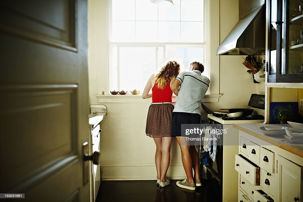 Couple standing looking out kitchen window : Stock Photo