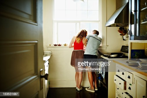 Couple standing looking out kitchen window : Foto de stock