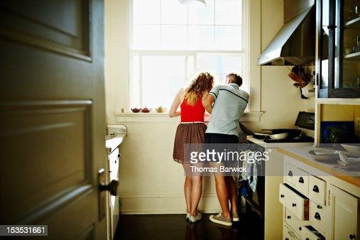 Couple standing looking out kitchen window : Bildbanksbilder