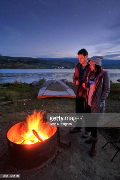 Couple standing near campfire. at dusk, drinking hot drinks