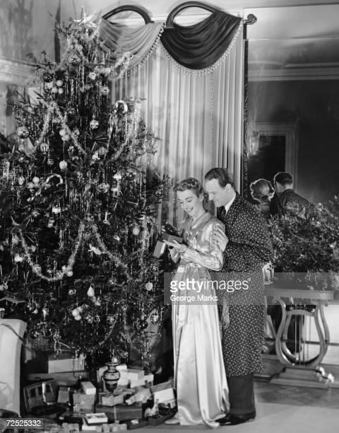 Couple standing near Christmas tree