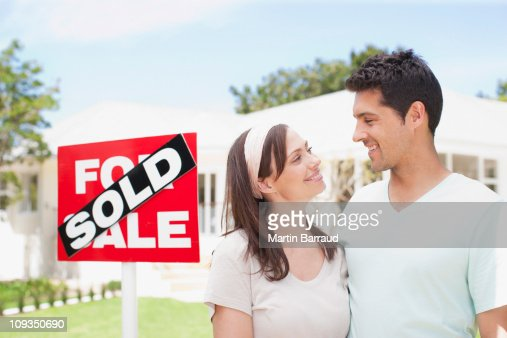 Couple standing near sold sign of their new house : Stock Photo