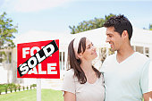 Couple standing near sold sign of their new house