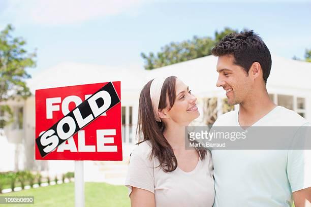 Paar stehen in der Nähe von Verkauf Zeichen für ihr neues Haus