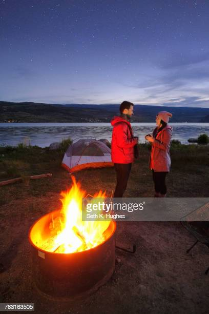 Couple standing near tent and campfire. at dusk, drinking hot drinks