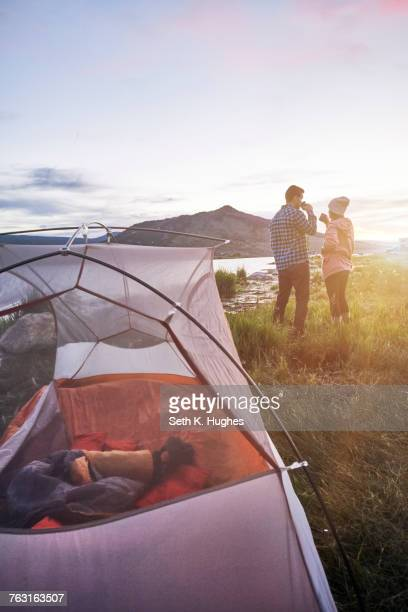 Couple standing near tent, drinking hot drinks, looking at view, Heeney, Colorado, United States