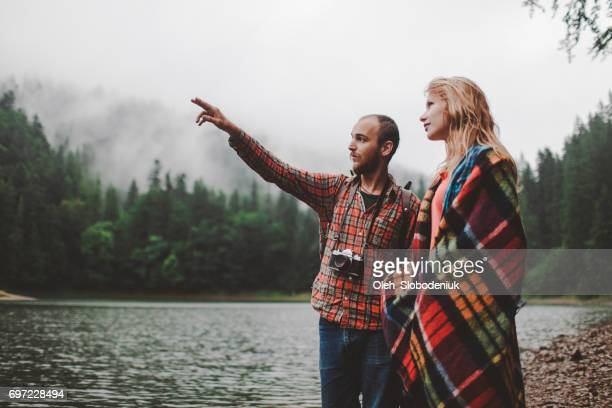 Couple standing near the lake in mountains