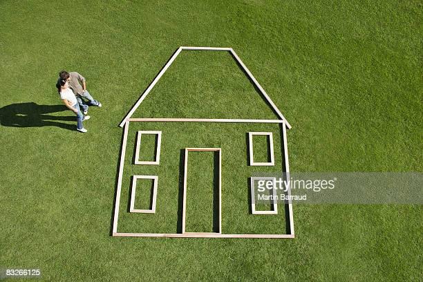 Coppia in piedi accanto a casa contorno