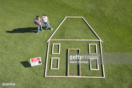 Couple standing next to house outline : Stock Photo