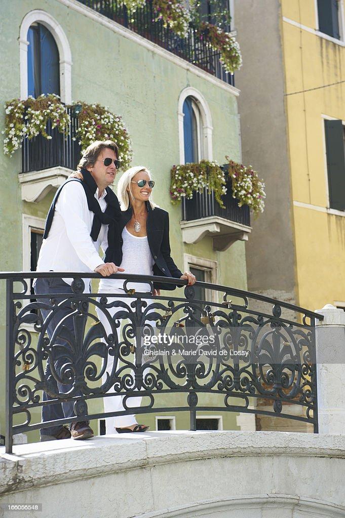 Couple standing on a bridge, smiling : Stock Photo
