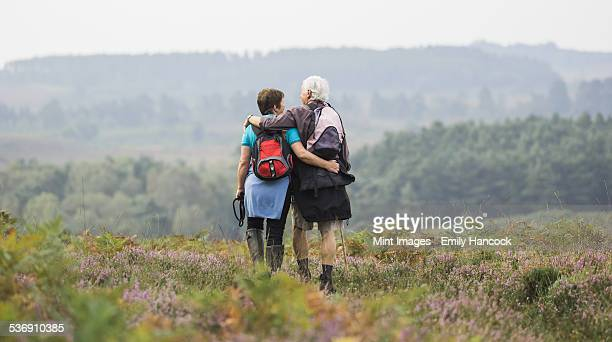 A couple standing on a path looking at the view over wooded hills, with arms around each other.