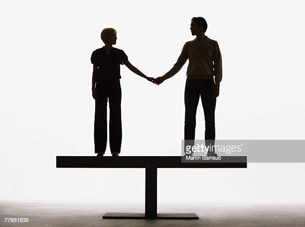 Couple standing on a plank holding hands