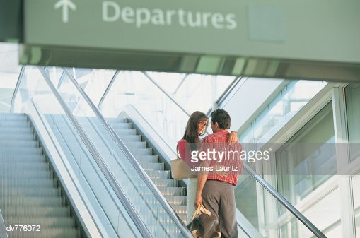 Couple Standing on an Airport Escalator Sad at Departing From Each Other : Stock Photo