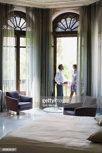 Couple standing on balcony of hotel room