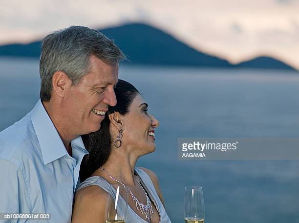 Couple standing on balcony with champagne