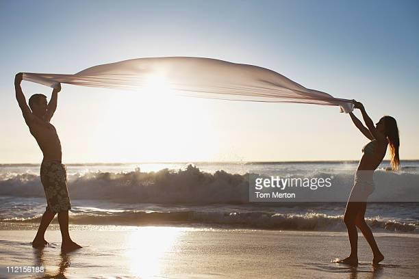Casal em pé na praia e segurar Tecido