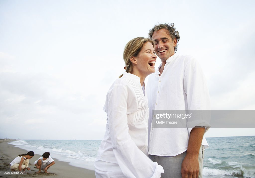 Couple standing on beach, smiling, children (7-9) in background
