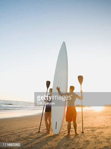 Couple standing on beach with surfboard and paddles : Stock Photo
