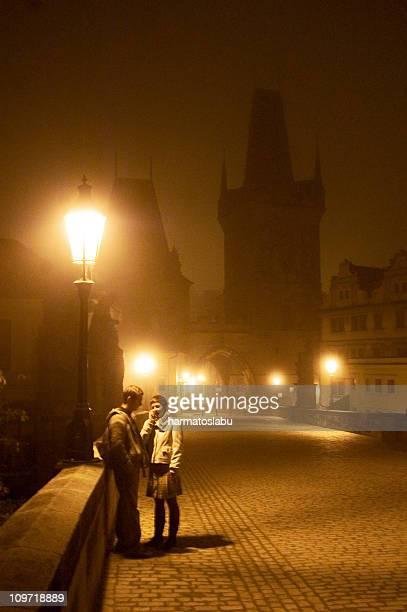 カップルの上に立つプラハの夜の橋