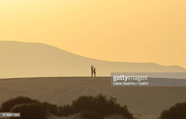 Couple Standing On Dune At Sunset